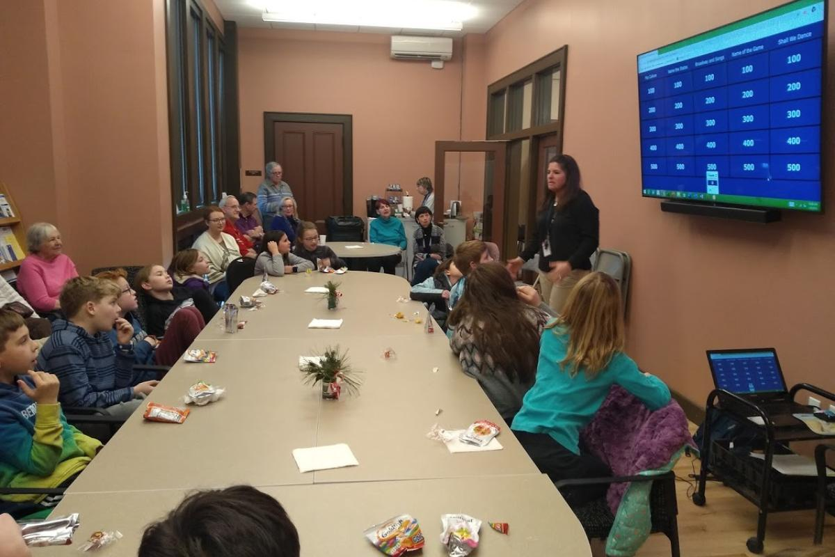 A Teacher Explains the Rules of a Game during an Intergenerational Event