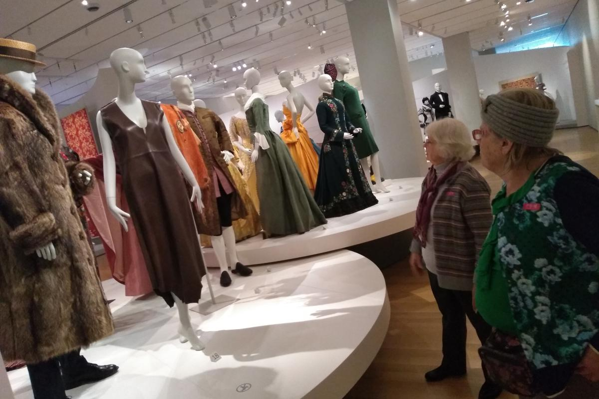 Two Women View a Display of Clothing at a Museum