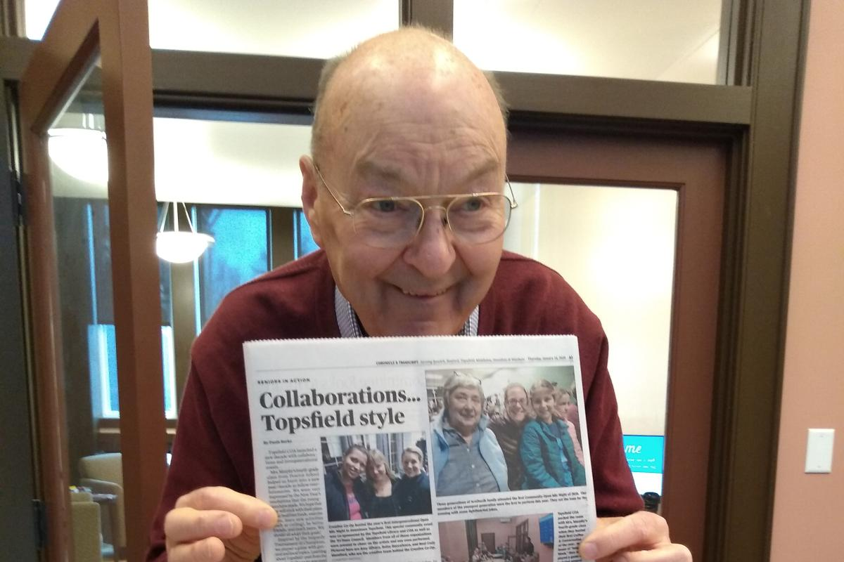 A Man Shows Off a Page in a Newspaper