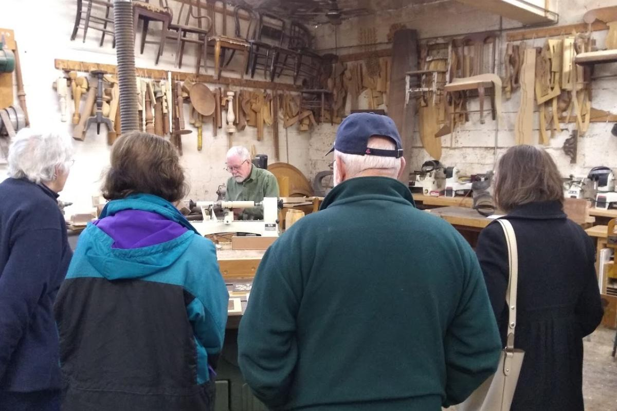 A Woodworker Demonstrates How to Use a Lathe to an Engaged Audience