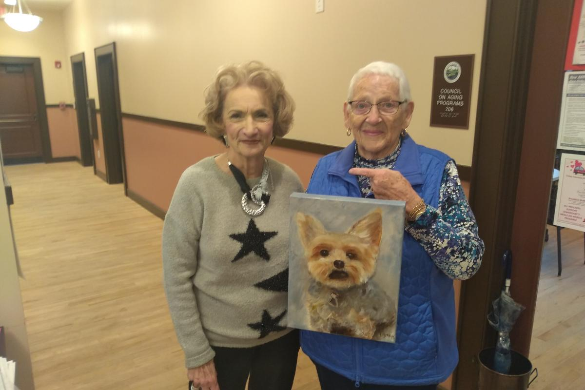 Two Women Hold Up Painting of Dog