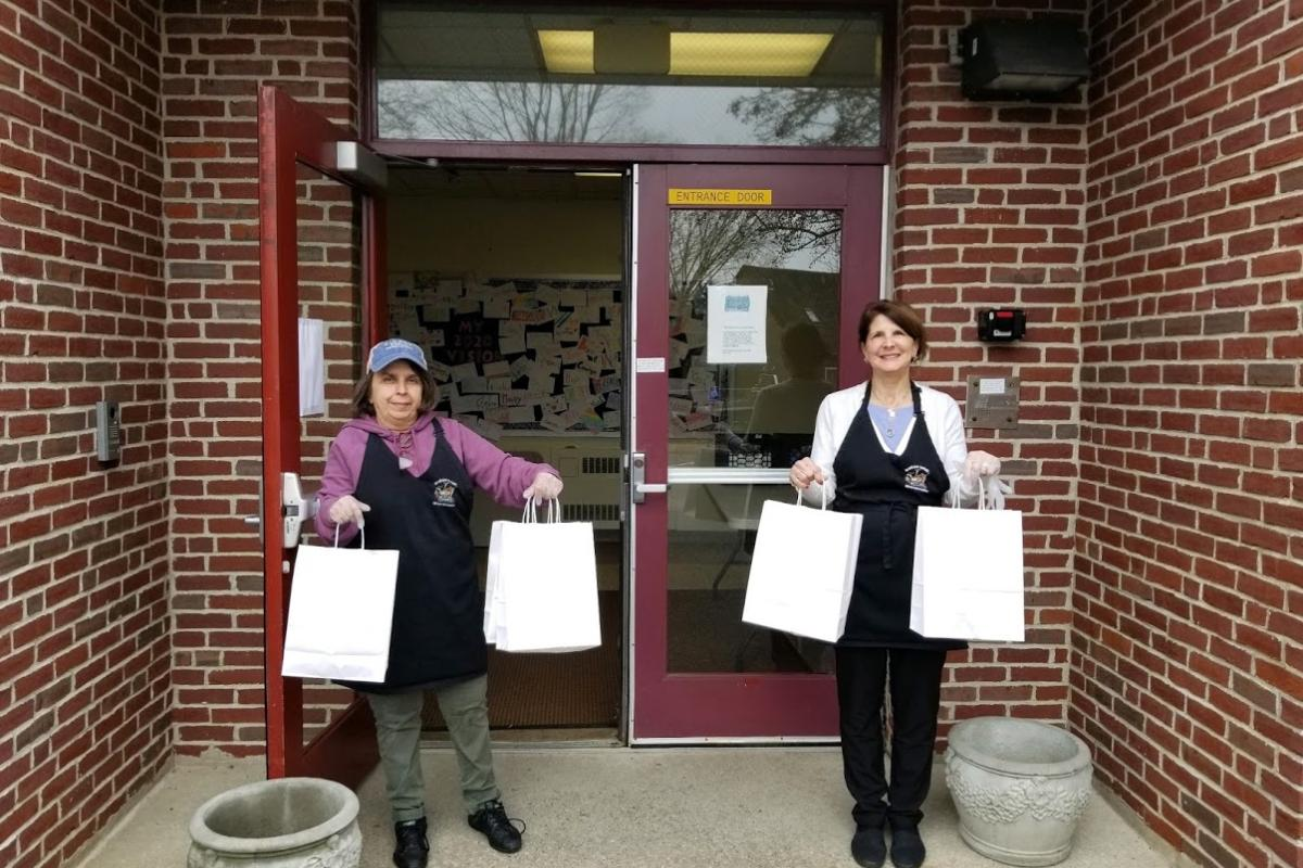 Two Women Hold Out Paper Bags