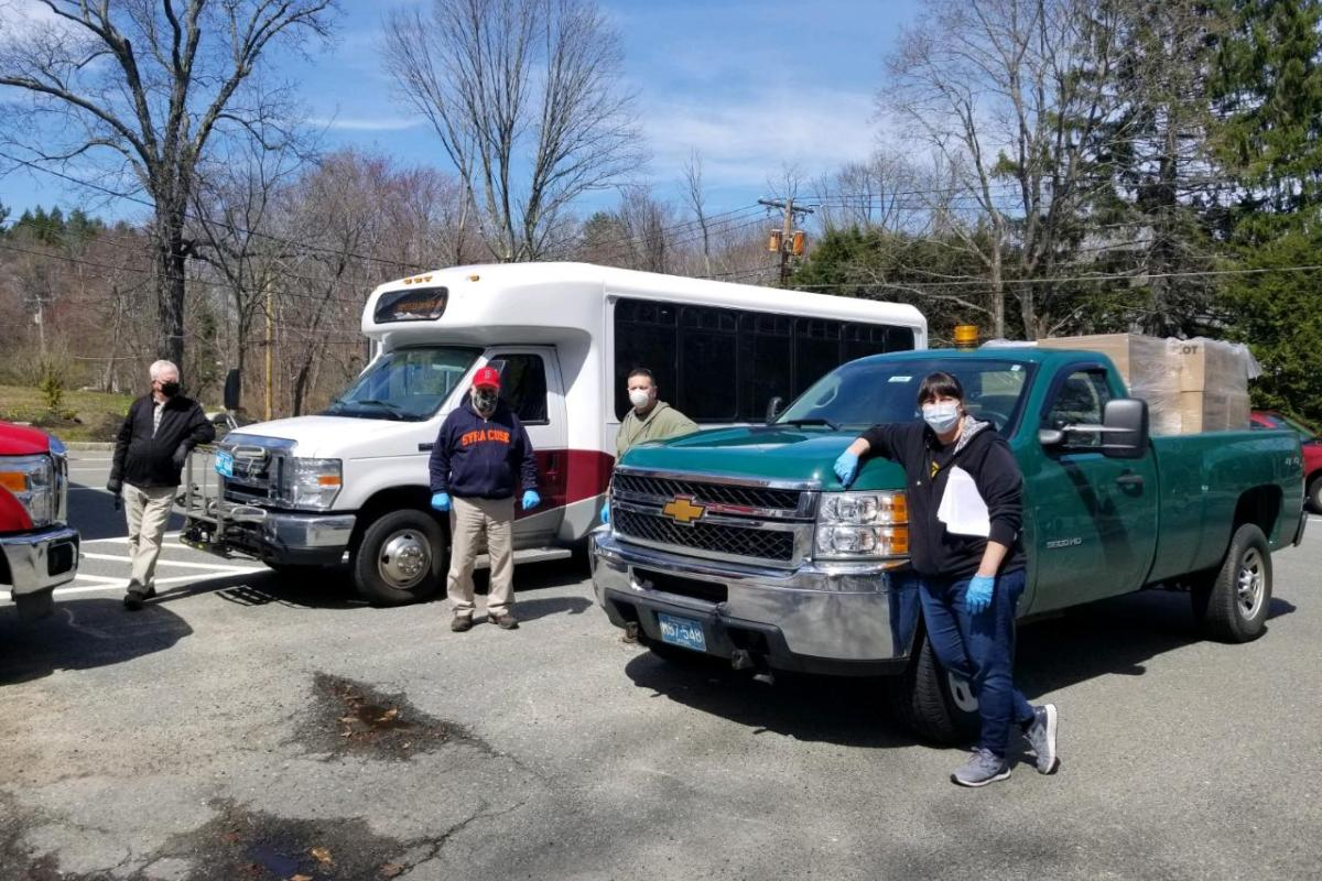 Four People Stand in Front of a Small Bus and a Pick-Up Truck
