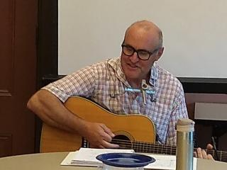 Man with guitar leads sing-along