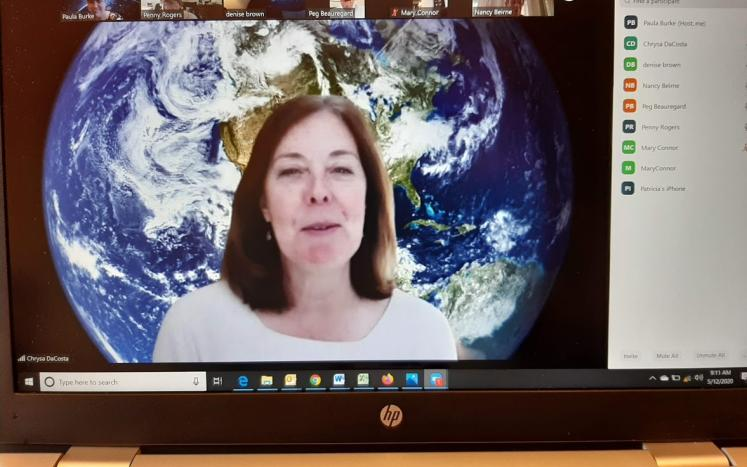 A virtual meeting is led by a woman with a large earth in the background